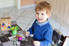 Little toddler boy being happy about selfmade Easter egg in kind Royalty Free Stock Photography