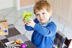Little toddler boy being happy about selfmade Easter egg in kind Royalty Free Stock Image
