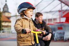 Little toddler boy with bicycle and his father in the city Royalty Free Stock Photography
