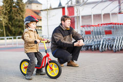 Little toddler boy with bicycle and his father in the city Royalty Free Stock Images