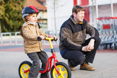 Little toddler boy with bicycle and his father in the city Royalty Free Stock Photo