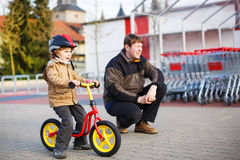 Little toddler boy with bicycle and his father in the city Royalty Free Stock Photos