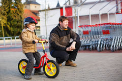 Little toddler boy with bicycle and his father in Royalty Free Stock Images