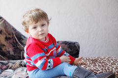 Little toddler boy with blue eyes and blond hairs indoor . Stock Images