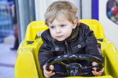 Little toddler boy on car on playground Stock Photo