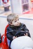 Little toddler boy on car on playground Stock Photo