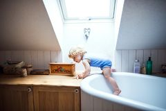 Toddler boy in a dangerous situation in the bathroom. Little toddler boy climbing out of bathtub. Domestic accident. Dangerous situation in the bathroom Stock Image