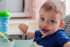 Little toddler boy with dirty face eating fresh blueberry indoor. Vitamins and health Royalty Free Stock Photos