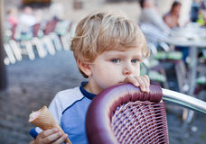 Little toddler boy eating ice cream in cone Royalty Free Stock Image