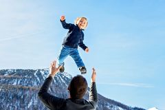 Little toddler boy, flying in the sky, dad throwing him high in the air. Family, enjoying winter view of snowy mountains and stock photos