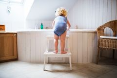 Toddler boy in a dangerous situation in the bathroom. Little toddler boy getting into a bathtub. Domestic accident. Dangerous situation in the bathroom. Rear royalty free stock photo