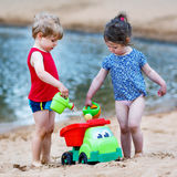 Little toddler boy and girl playing together with sand toys near Royalty Free Stock Image