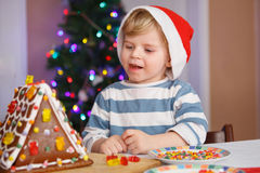 Little toddler boy happy about gingerbread cookie house Royalty Free Stock Images
