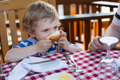 Little toddler boy having breakfast in summer Stock Images