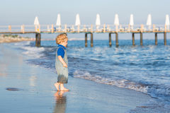 Little toddler boy having fun on the beach in summer Stock Photos