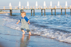 Little toddler boy having fun on the beach in summer Royalty Free Stock Photo