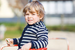Little toddler boy having fun on old carousel on outdoor playgro Stock Photo