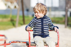 Little toddler boy having fun on old carousel on outdoor playgro Stock Image