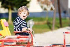 Little toddler boy having fun on old carousel on outdoor playgro Royalty Free Stock Photo