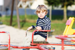 Little toddler boy having fun on old carousel on outdoor playgro Royalty Free Stock Photography