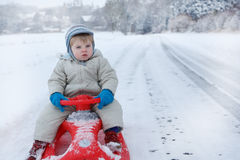 Little toddler boy having fun with snow outdoors on beautiful wi Stock Photos