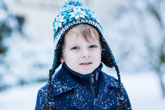 Little toddler boy having fun with snow outdoors on beautiful wi Stock Images