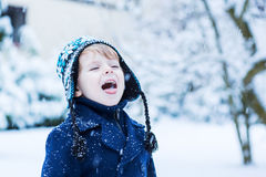 Little toddler boy having fun with snow outdoors on beautiful wi Stock Image