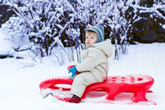 Little toddler boy having fun with snow outdoors on beautiful wi Royalty Free Stock Photo