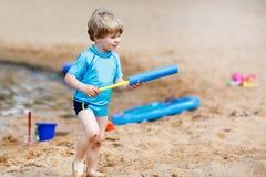 Little toddler boy having fun with splashing water near city lak Stock Photos