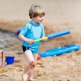 Little toddler boy having fun with splashing water near city lak Royalty Free Stock Photography