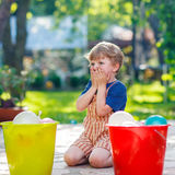 Little toddler boy having fun with splashing water in summer gar Stock Images