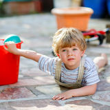 Little toddler boy having fun with splashing water in summer gar Royalty Free Stock Image