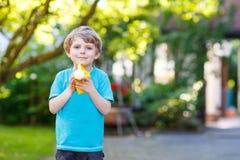 Little toddler boy having fun with splashing water in summer gar Stock Images