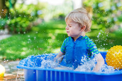 Little toddler boy having fun with splashing water in summer gar Royalty Free Stock Photos