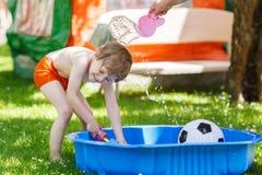 Little toddler boy having fun with splashing water in summer gar Stock Photo