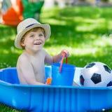 Little toddler boy having fun with splashing water in summer gar Royalty Free Stock Photography