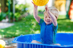 Little toddler boy having fun with splashing water in summer gar Stock Photography