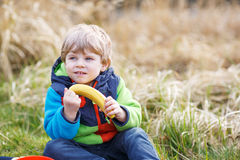 Little toddler boy having picnic near forest lake, nature Stock Photos