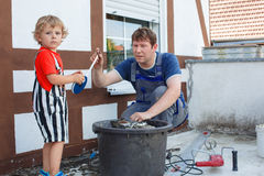 Little toddler boy helping his father with renovation of home. Little blond toddler boy helping his father with renovation of home royalty free stock photo