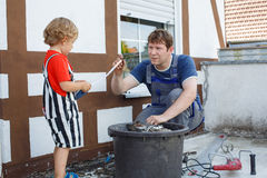 Little toddler boy helping his father with renovation of home. Little blond toddler boy helping his father with renovation of home stock image