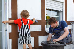 Little toddler boy helping his father with renovation of home. Little blond toddler boy helping his father with renovation of home Stock Images