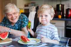 Little toddler boy and his great grandmother eating watermelon a. Little toddler boy and his great grandmother eating watermelon in home kitchen. Selective focus Stock Images