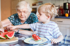 Little toddler boy and his great grandmother eating watermelon a. Two generations: Little boy and his great grandmother eating watermelon in home kitchen Royalty Free Stock Photo
