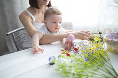 Little toddler boy and his mother decorating Easter egg Stock Photos
