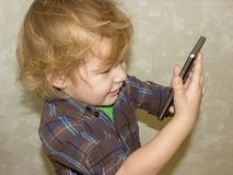 A little toddler boy holds a gadget in his hands and clicks on the smartphone screen. A satisfied child is happy that he was allowed to play with his parent stock photos