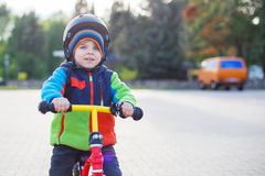Little toddler boy learning to ride on his first bike Stock Images