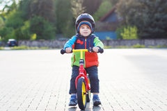 Little toddler boy learning to ride on his first bike Stock Photo