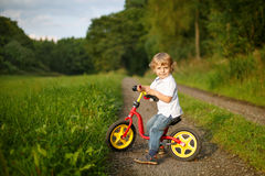 Little toddler boy learning to ride on his first bike Stock Photos