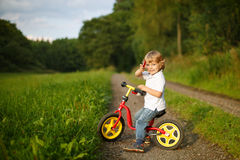 Little toddler boy learning to ride on his first bike Royalty Free Stock Image