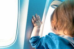 Toddler boy looking out a plane window. Little toddler boy looking out an airplane window while flying Royalty Free Stock Photography